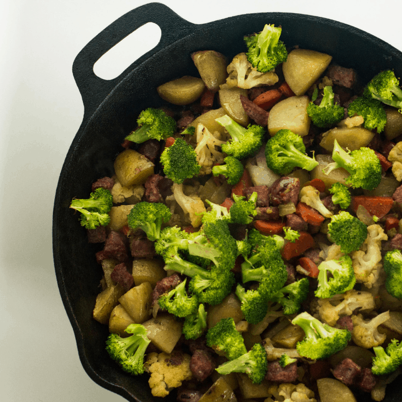potatoes sausage and veggies in a cast iron skillet with a white background