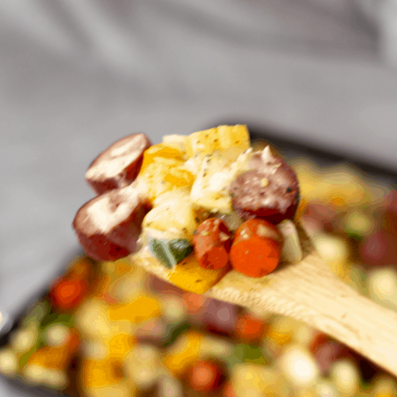 autum veggies with sausage sheet pan dinner, a wooden spoon holding up a spoonful